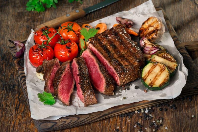 Bistecca arrostita rara affettata con le verdure arrostite vicino su fotografia stock libera da diritti