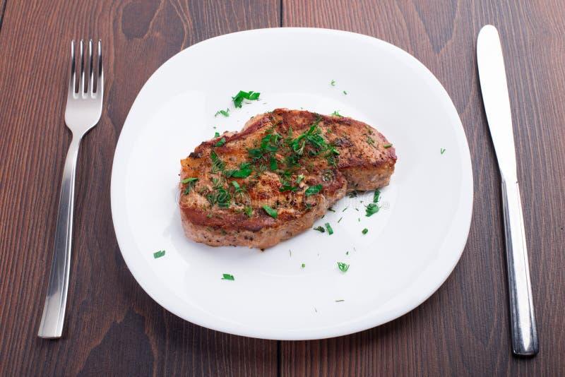 Bistecca arrostita sul piatto bianco fotografie stock