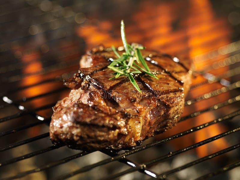 Bistecca che cucina sopra la griglia ardente immagini stock libere da diritti