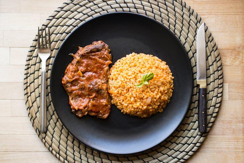 Bistecca con il riso del bulgur e della salsa al pomodoro in una banda nera fotografie stock libere da diritti