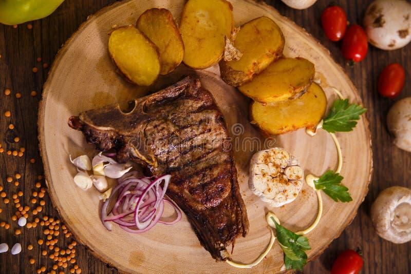Bistecca con l'osso della bistecca su protezione di legno e sulle patate al forno immagini stock