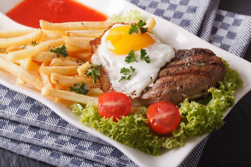 Bistecca con l'uovo fritto e le fritture su un primo piano del piatto horizonta fotografie stock libere da diritti