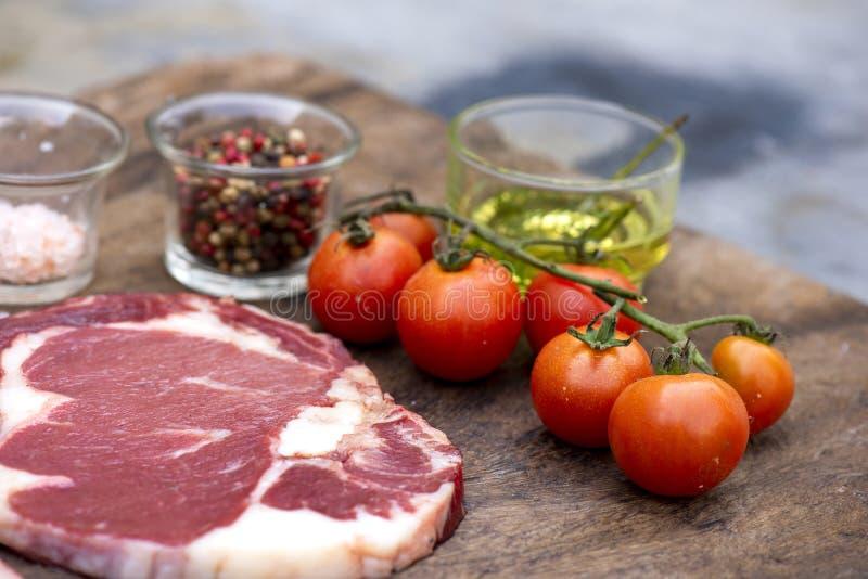Bistecca cruda con le spezie e gli ingredienti per cucinare fotografia stock libera da diritti