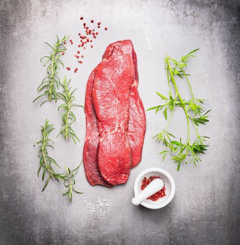 Bistecca cruda della carne del manzo con le erbe fresche su fondo di pietra grigio fotografia stock libera da diritti