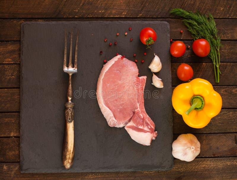 Bistecca cruda fresca cruda della carne suina sull'osso sul choppi della pietra dell'ardesia fotografie stock libere da diritti