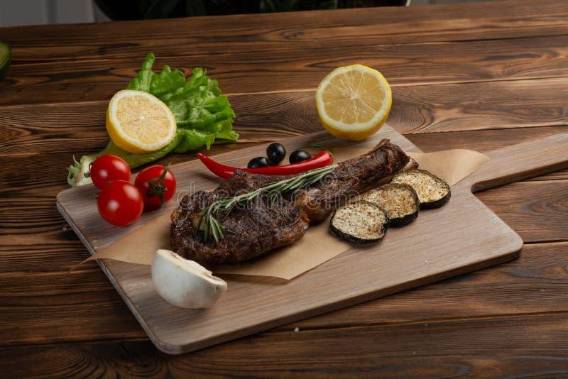 Bistecca dell'agnello con le verdure e la salsa al pomodoro su un fondo di legno fotografia stock