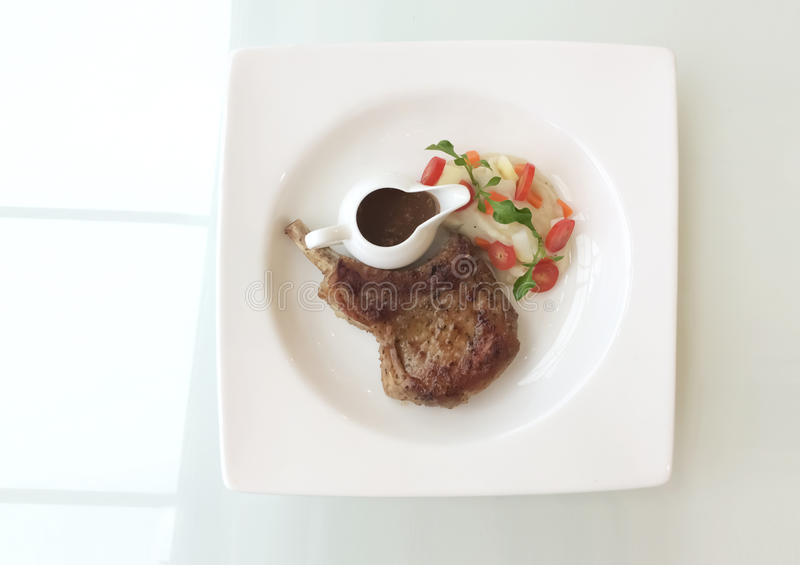 Bistecca della carne di maiale con la salsa e la verdura del sugo immagini stock