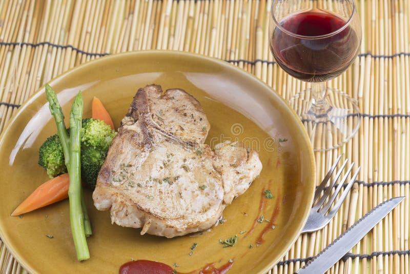 Bistecca della carne di maiale della bistecca con l'osso e vino rosso immagini stock