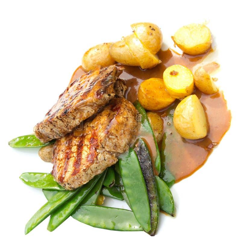 Bistecca della carne servita con la patata ed i piselli Isolato fotografia stock libera da diritti