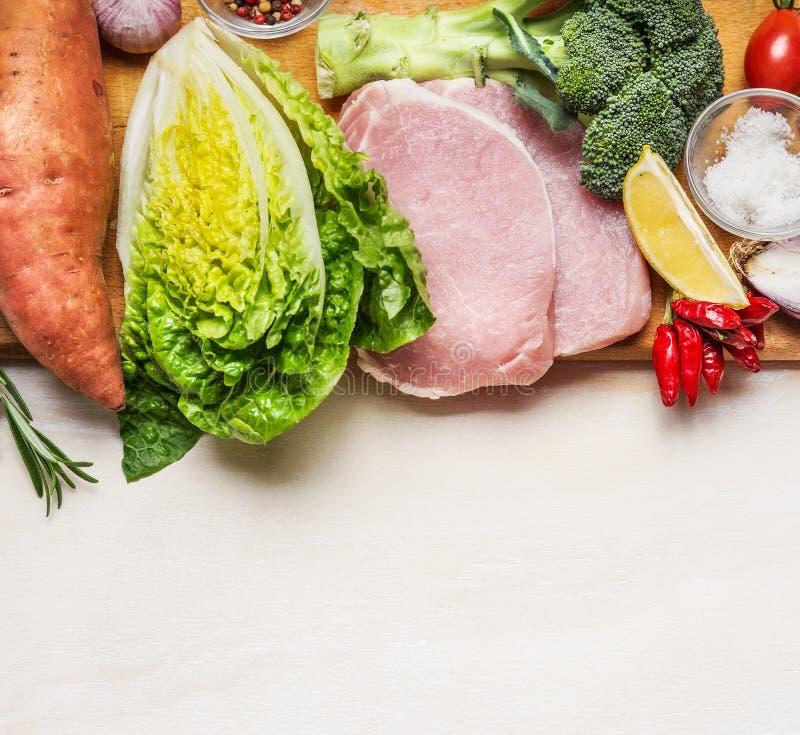 Bistecca della lonza di maiale con gli ortaggi freschi e gli ingredienti per la cottura sul fondo di legno bianco immagini stock