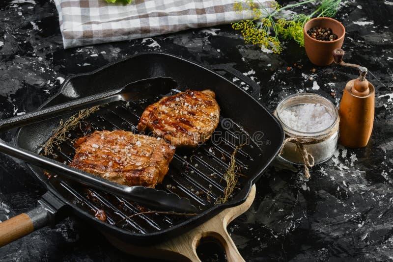 Bistecca di Angus fritta su olio vegetale su ferro fuso con i rosmarini ed il sale marino Immagine autentica di stile di vita Vis fotografia stock libera da diritti