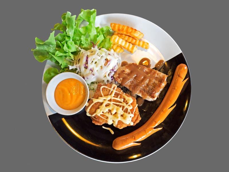 Bistecca di braciola di maiale con Fried Chicken, la salsiccia, le patate fritte ed il Sa fotografie stock