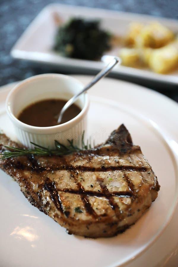 Bistecca di braciola di maiale con le patate arrostite aglio immagini stock
