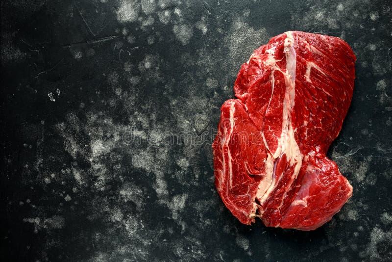 Bistecca di brasatura cruda fresca su fondo nero immagini stock