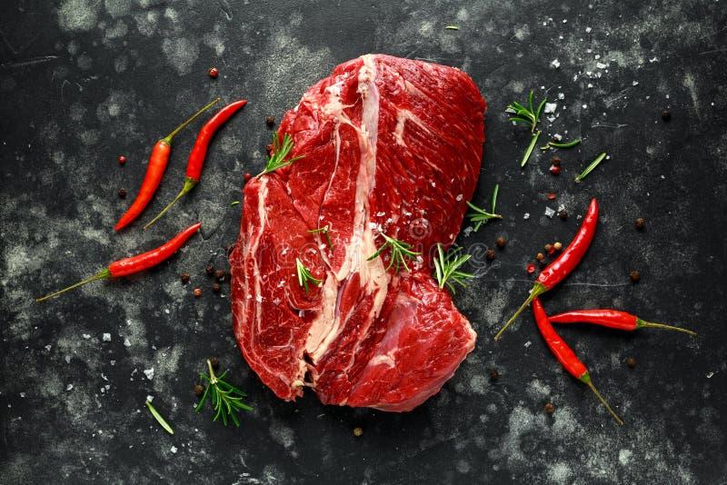 Bistecca di brasatura cruda fresca su fondo nero con i rosmarini, peperoncini rossi, pepe fotografia stock