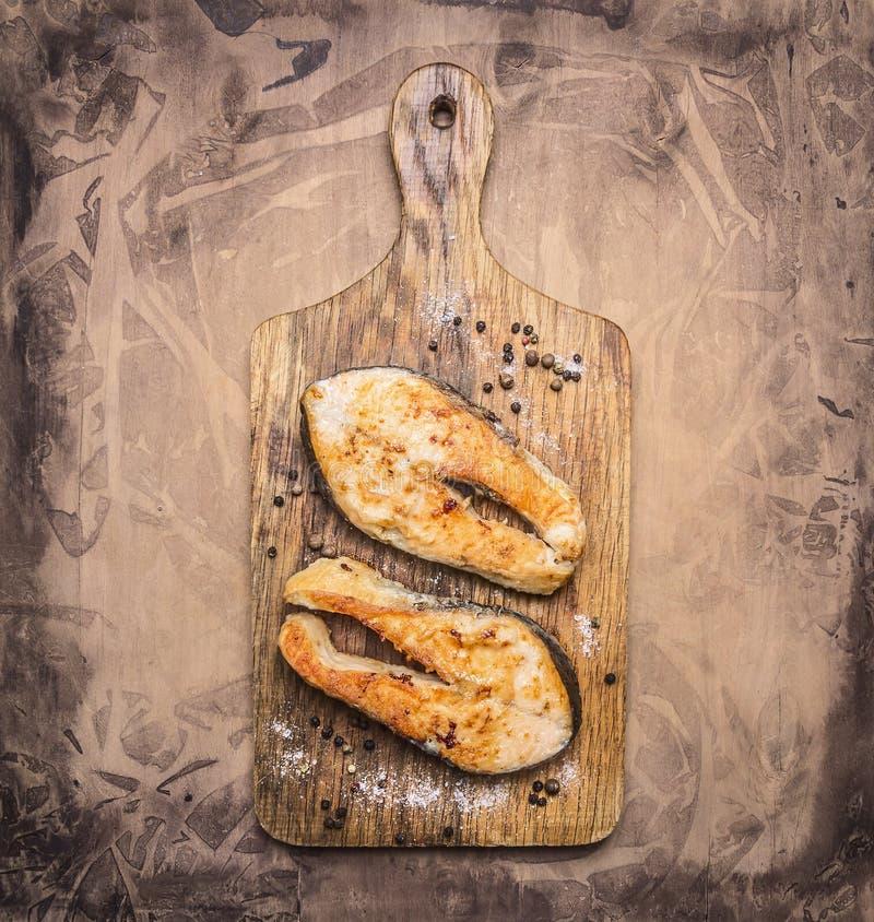 Bistecca di color salmone arrostita deliziosa due con le spezie su una fine rustica di legno di vista superiore del fondo del tag fotografia stock libera da diritti