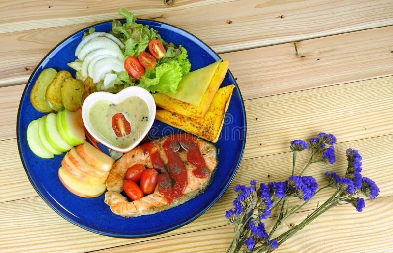 Bistecca di color salmone con i piatti laterali in piatto blu fotografia stock