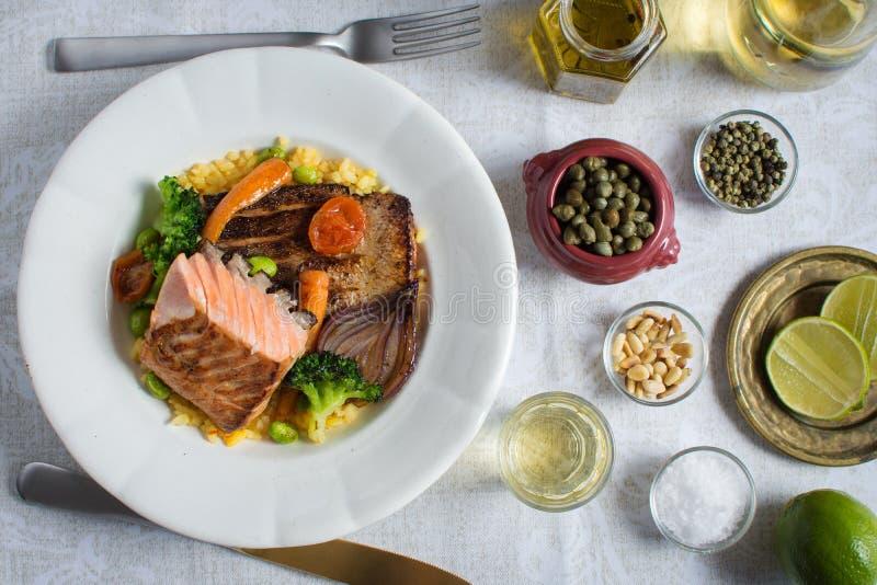 Bistecca di color salmone cotta con le verdure sul piatto bianco immagine stock