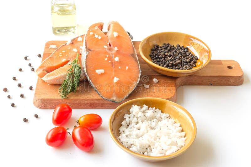 Bistecca di color salmone cruda di color salmone del pesce fresco con il pepe del sale marino e l'erbaccia di aneto isolati su un fotografia stock