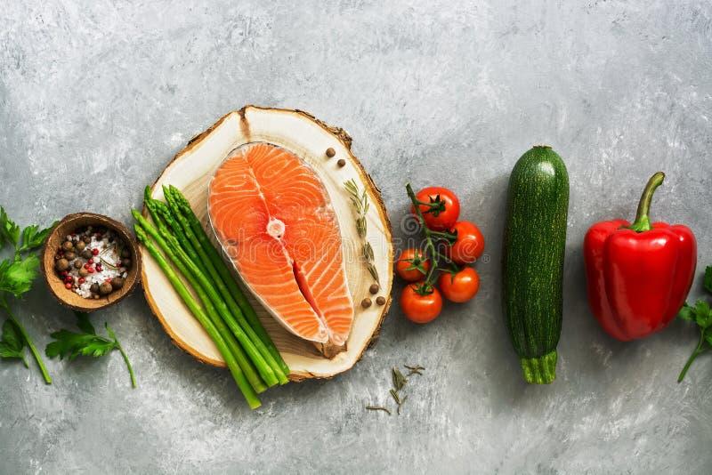 Bistecca di color salmone cruda e ortaggi freschi di disposizione piana in una fila su fondo grigio Vista superiore, spazio della immagini stock libere da diritti