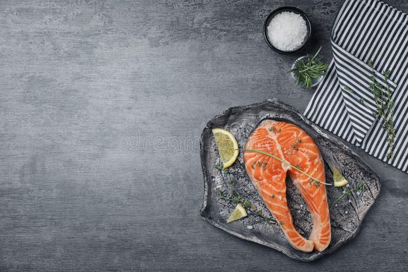 Bistecca di color salmone cruda fresca con i condimenti fotografia stock