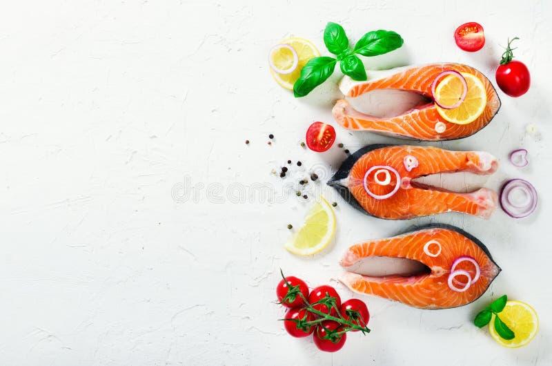 Bistecca di color salmone fresca cruda con le verdure Ingredienti per la cottura sul fondo bianco Spazio per testo Dieta e sano fotografia stock libera da diritti