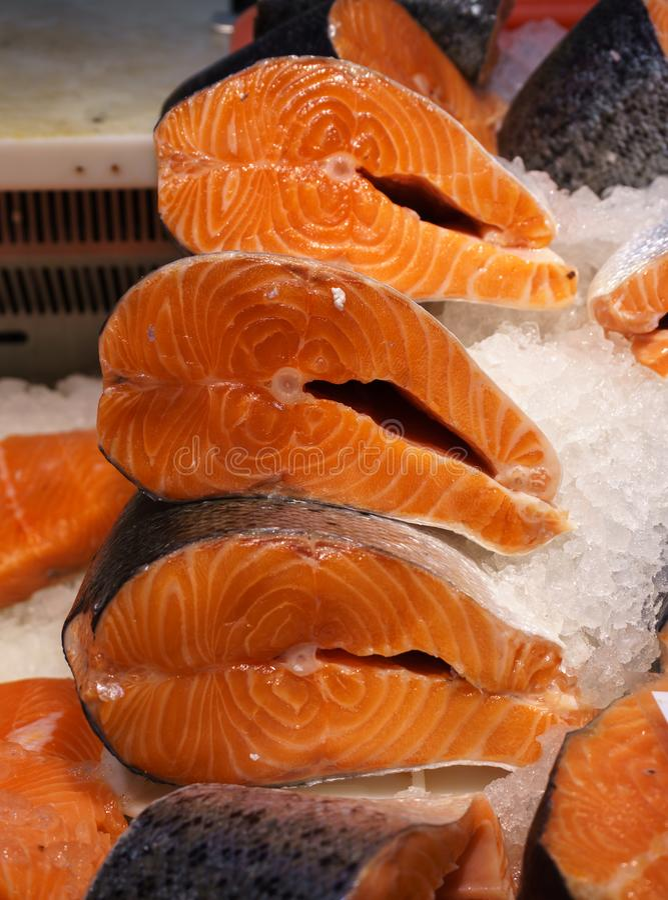 Bistecca di color salmone fresca da vendere nel ghiaccio Pesce rosso Vetrina di un deposito del pesce immagine stock libera da diritti