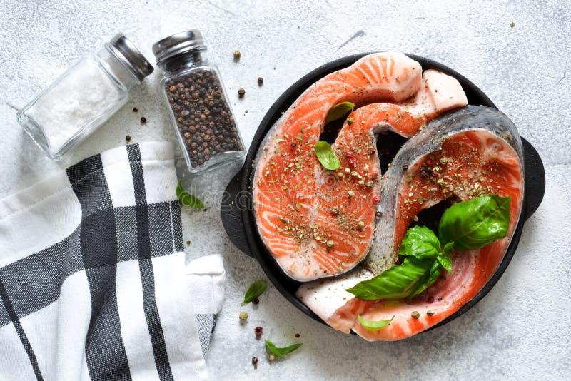 Bistecca di color salmone fresca e cruda con le spezie su un fondo bianco Vista da sopra immagini stock libere da diritti