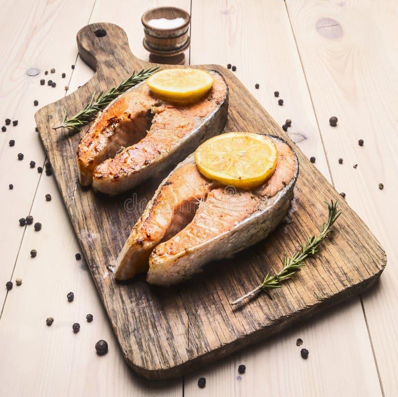 Bistecca di color salmone fritta appetitosa su un tagliere con del limone, dei rosmarini e del pepe la fine unground su fotografia stock