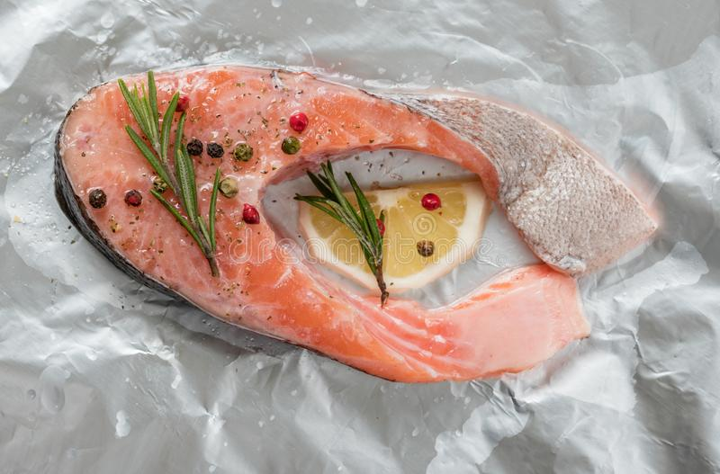 Bistecca di color salmone grezza Bistecca fresca della trota con le spezie sulla stagnola, pronta da cuocere Alimento sano e sapo immagine stock