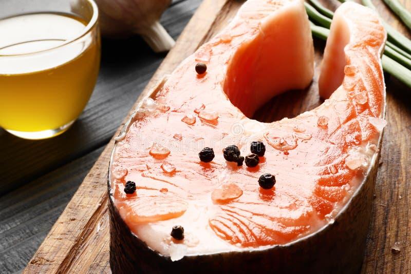 Bistecca di color salmone, pepe e sale, erbe sulla tavola nera fotografia stock