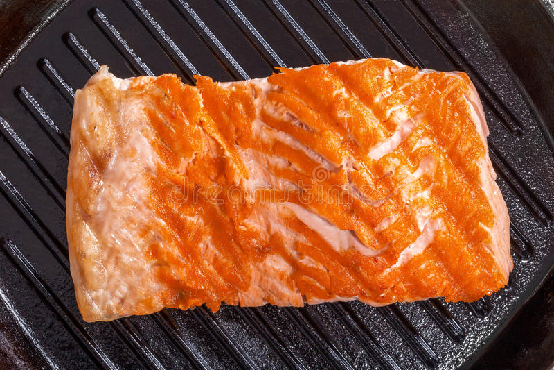 Bistecca di color salmone su una pentola del gril del ferro fotografia stock