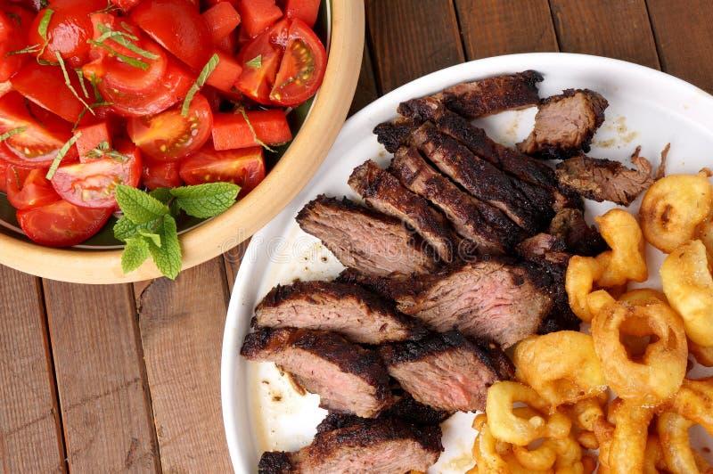 Bistecca di fianco con gli anelli e l'insalata di cipolla delle fritture fotografia stock