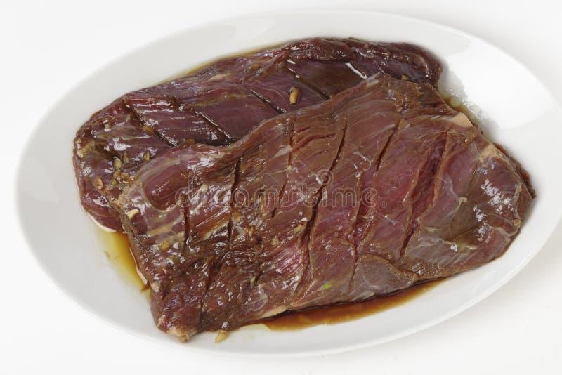 Bistecca di fianco marinata su un piatto fotografia stock