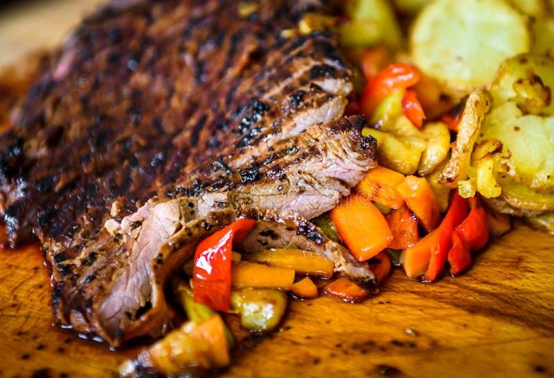 Bistecca di fianco marinata succosa arrostita affettata del manzo sul bordo di legno fotografia stock