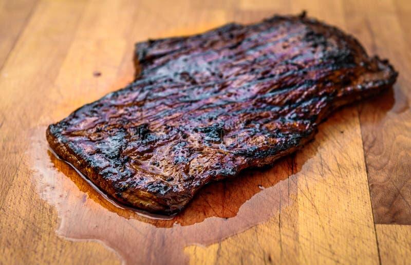 Bistecca di fianco marinata succosa arrostita del manzo sul bordo di legno fotografie stock libere da diritti