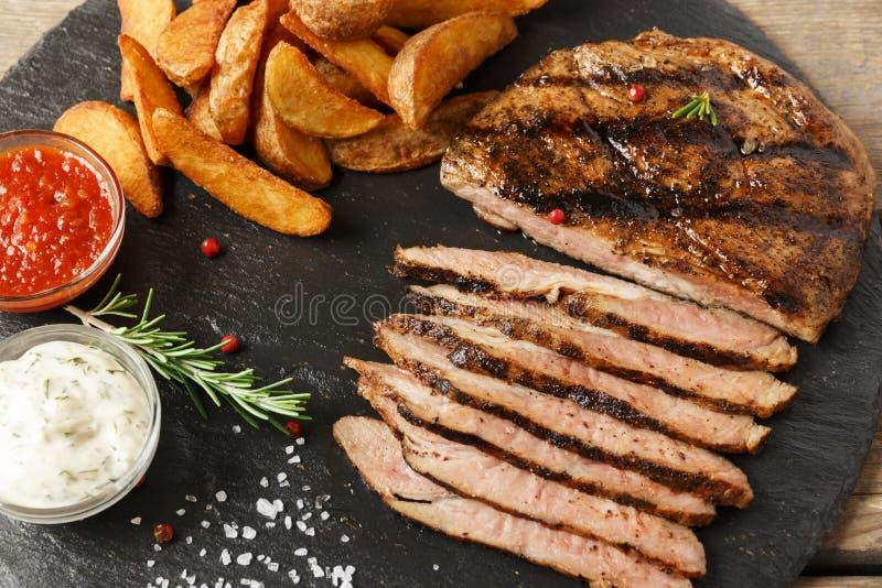 Bistecca di manzo affettata con la patata al forno e la salsa fotografia stock