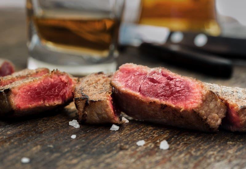 Bistecca di manzo arrostita affettata sulla tavola di legno con whiskey fotografia stock