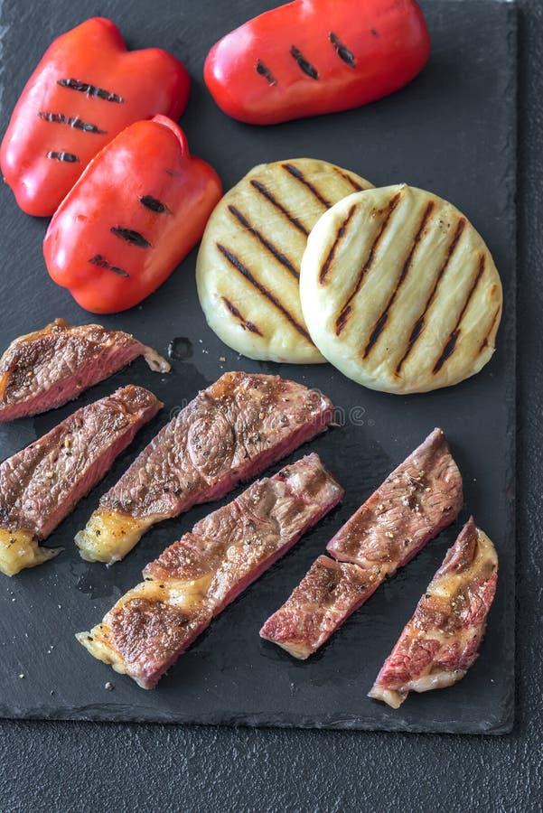 Bistecca di manzo arrostita con i peperoni dolci ed il formaggio immagine stock
