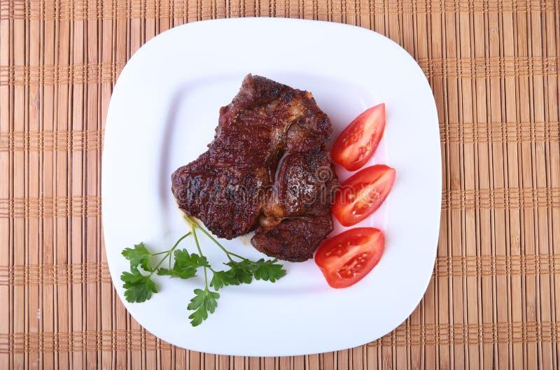 Bistecca di manzo arrostita con il pomodoro e salsa di aglio asiatica calda dei peperoncini rossi sul piatto su fondo di legno fotografia stock libera da diritti