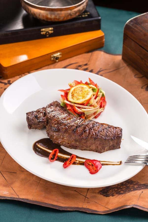 Bistecca di manzo arrostita con l'insalata ed il peperoncino di verdura fresca sul piatto bianco sul vecchio fondo della mappa fotografia stock
