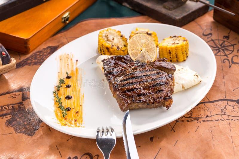 Bistecca di manzo arrostita con la tortiglia ed il cereale arrostito sul piatto bianco sul vecchio fondo della mappa fotografia stock libera da diritti
