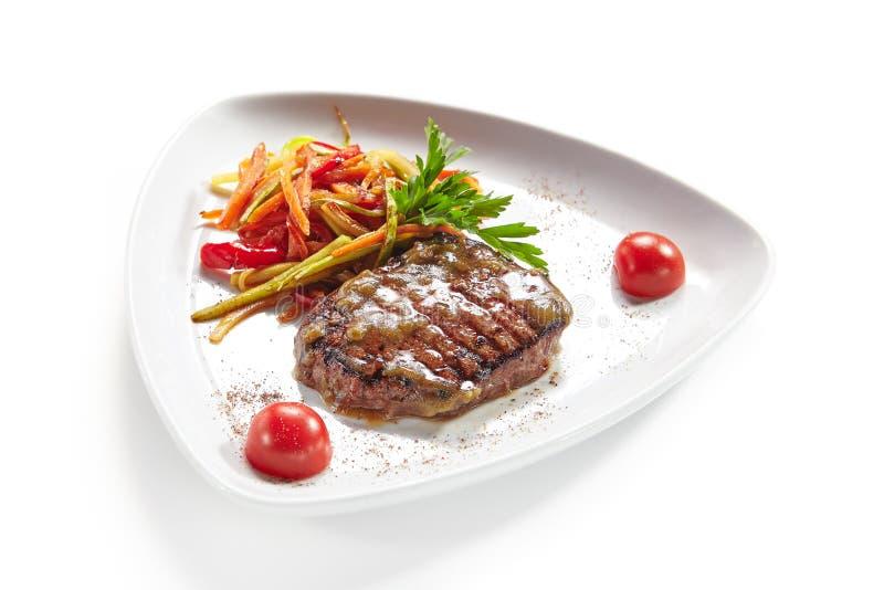 Bistecca di manzo arrostita con le verdure isolate su fondo bianco immagini stock