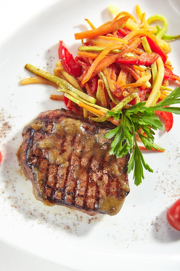 Bistecca di manzo arrostita con le verdure su fondo bianco fotografie stock