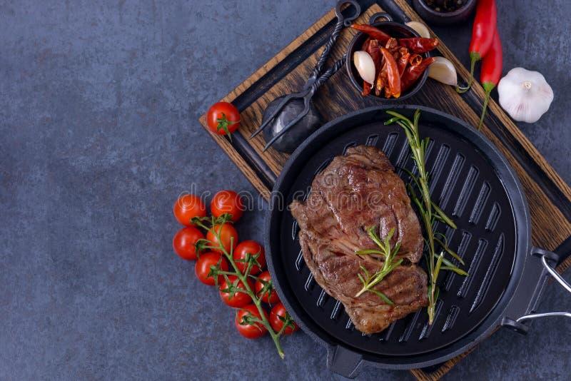 Bistecca di manzo arrostita dello striploin, pomodoro, erbe e spezie fotografia stock