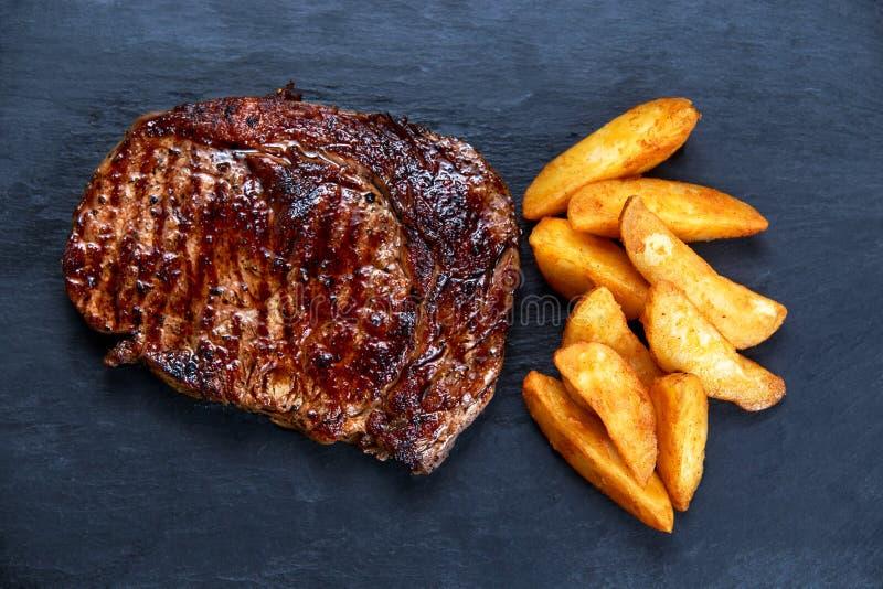 Bistecca di manzo arrostita rara media riscaldata sul posto Ribeye con la patata arrostita sul fondo della pietra blu fotografie stock