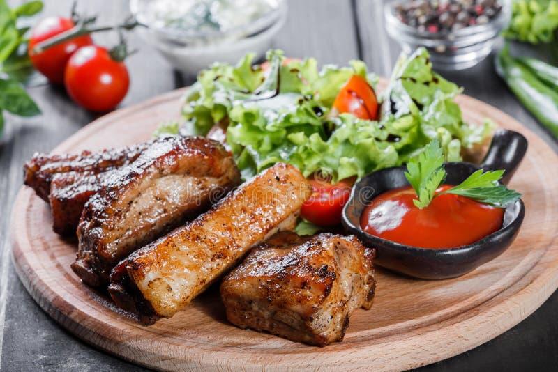 Bistecca di manzo arrostita Ribeye con l'insalata, i pomodori e la salsa della verdura fresca sul tagliere di legno immagine stock libera da diritti