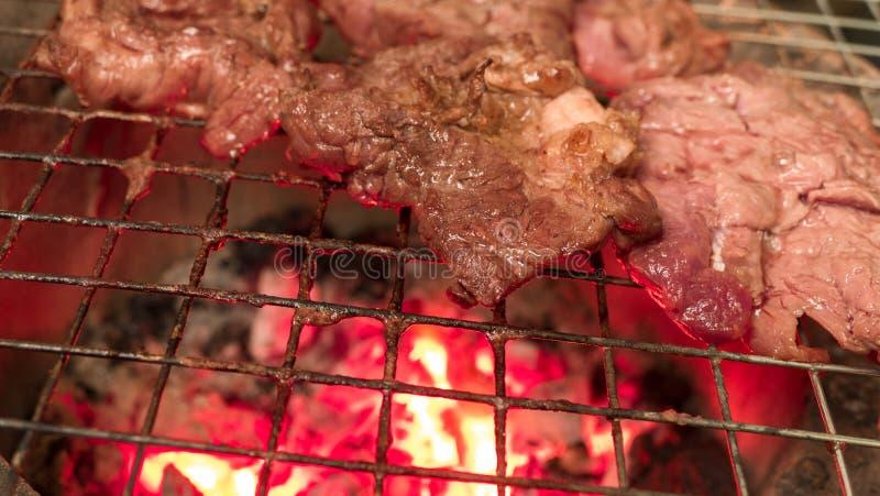 Bistecca di manzo che cucina sopra la griglia ardente fotografia stock libera da diritti