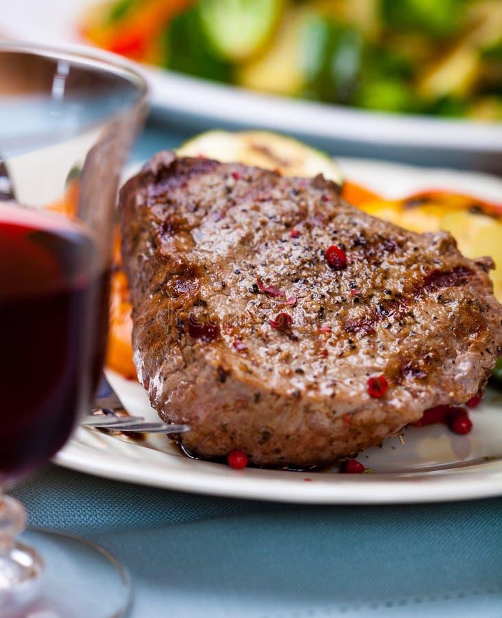 Bistecca di manzo cotta e un vetro di vino rosso fotografia stock libera da diritti