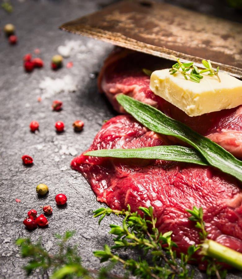 Bistecca di manzo cruda con le erbe fresche, le spezie, il burro e la vecchia mannaia immagini stock libere da diritti